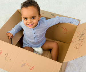 Child playing in a cardboard box