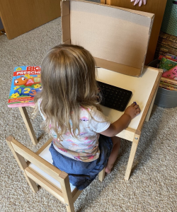 Child playing with a pretend computer