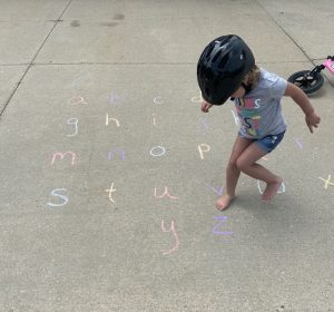 Child playing sidewalk chalk letter game